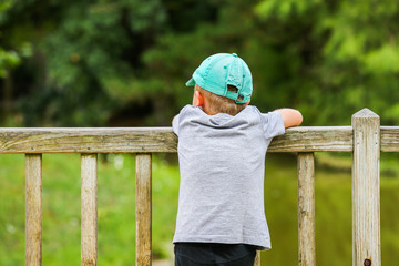 A little boy leaning over a fence