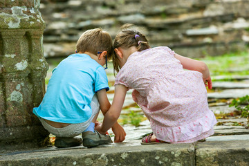 Two kids playing on the ground next to a mossy stone