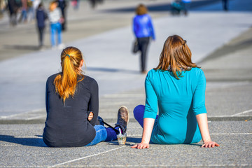 Two girls chilling out on the ground