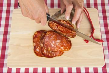 Carnicero cortando lonchas de morcón ibérico sobre la tabla
