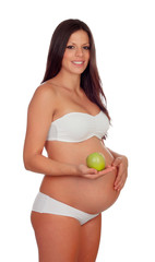 Brunette pregnant in underwear with a green apple