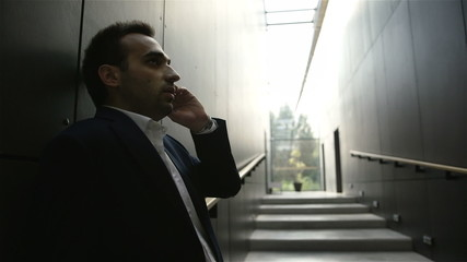 Businessman talking by mobile phone in the office hall