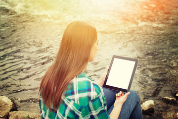 Teenage girl with tablet sitting by the river in autumn