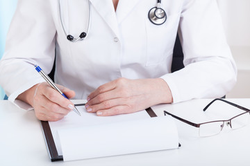Doctor making notes in office