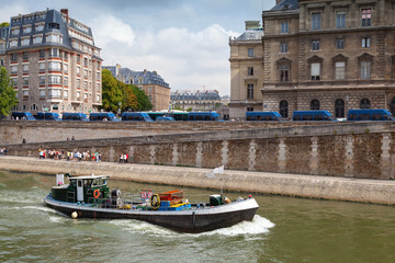 Small industrial boat sails along the quay of river Seine, Paris