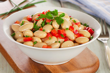 Salad with white beans on  wooden board.