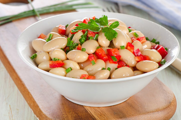 Salad with white beans on a wooden board.