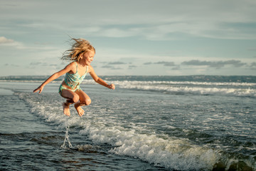 little girl running on the beach at the day time