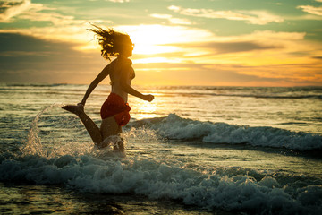 woman running at the beach in the dawn time