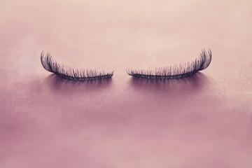 Close up false eyelashes on pink background