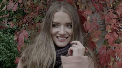 Pretty caucasian woman in autumn park enjoying nature.