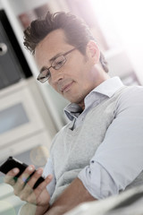Relaxed businessman in office using smartphone