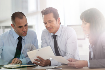 Business people meeting around desk with tablet