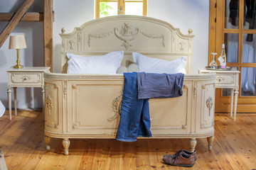 Old Bed with a man's suit and shoes