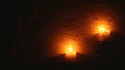 two candles on the dark, concrete wall