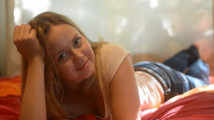 Cute young woman lying on bed looking at camera and smiling