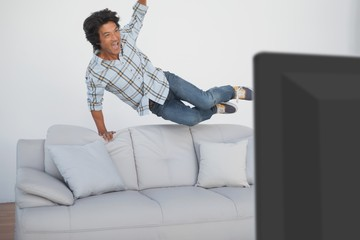 Happy soccer fan cheering while watching tv