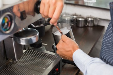 Barista steaming milk at the coffee machine
