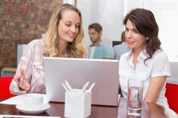 Happy businesswomen looking at computer screen together