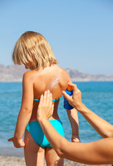 Mother applying sunscreen to her child