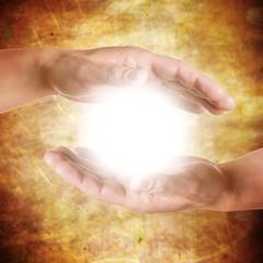 Hände halten strahlendes Licht - Meditation