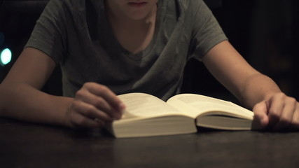 Teenager reading book by the table at night