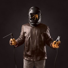 welder in protective helmet with welding apparatus in the hands