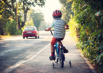 Boy on bike on sidewalk