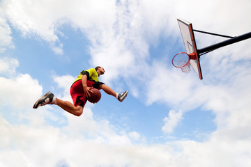 Young man making a slam dunk playing streetball basketball