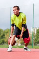 Young man on basketball court dribbling with ball