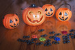 canvas print picture - Halloween pumpkins on wooden with spider and skulls