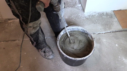worker mix adhesive cement for tile on bucket with tool