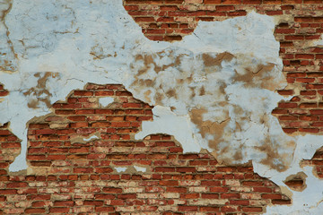 Old weathered plaster on the brick Wall