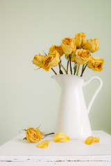 Yellow roses in a white enamel jug