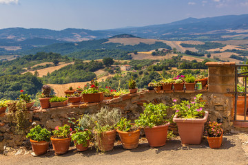 View over Tuscany Hills, Pots of Flowers are lined along the Bal