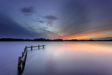 Winter Sunset over Tranquil Lake with Wooden Mooring Post