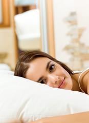 Young woman waking up on bed