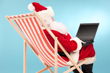 Santa working on laptop seated in a sun lounger