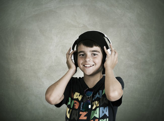 child with current clothing with headphones listening to music
