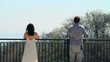 Couple looking at beautiful view from terrace on sunny day