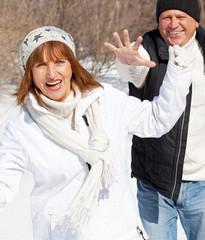 Happy seniors couple in winter park