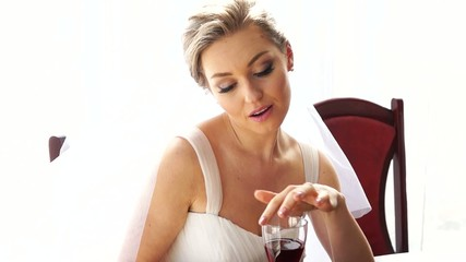 Young woman in white dress, drinks wine from glass.