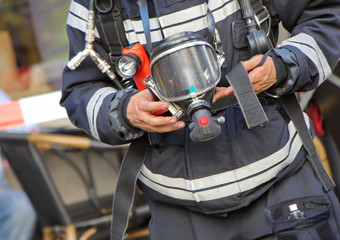 Firefighter holding oxygen or gas mask