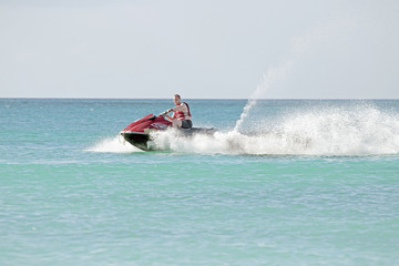 Young guy cruising on the caribbean sea on a jet ski