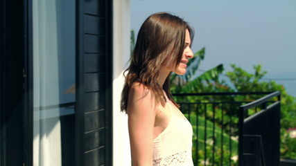 Attractive woman walk out on terrace, enjoy sunny day