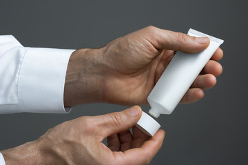 Man's hands with  white cream tube