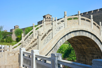 Arch bridge and the wall of an ancient fortress.