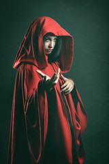Dark portrait of a beautiful woman with red cloak