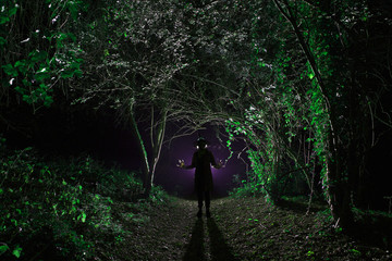 Silhouette witch in the woods