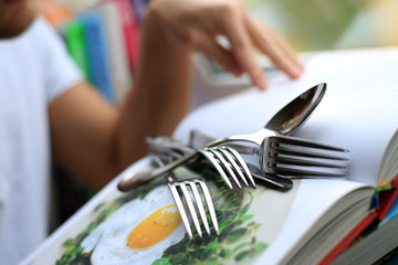 Kitchenware on the book with recipes, fork and spoon